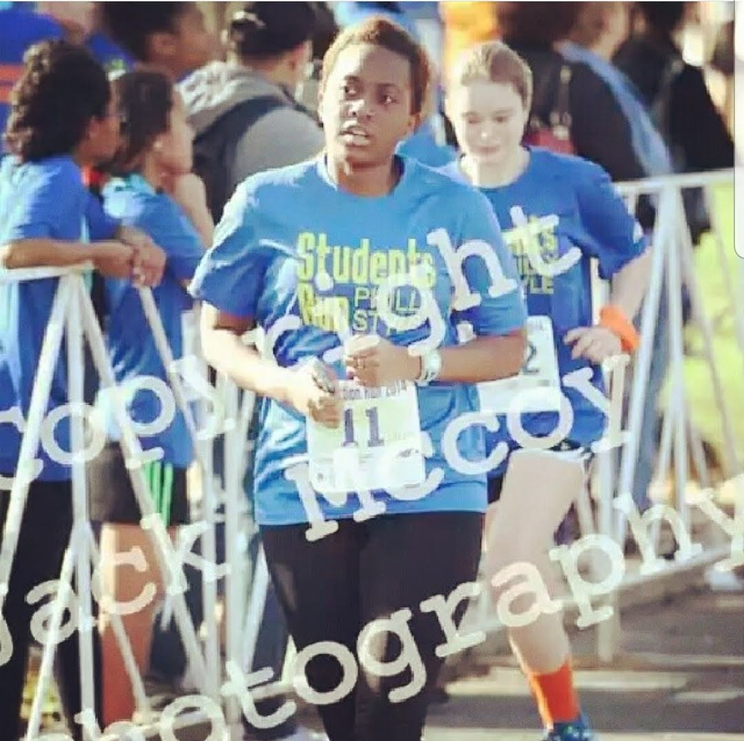 Girl running in a race with a watermark overlaying it